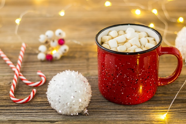 Red cup of hot cocoa with marshmallows white balls and candy canes. background with beautiful christmas lights bokeh.