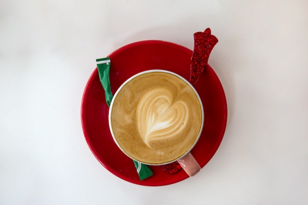 Red cup of hot coffee with heart