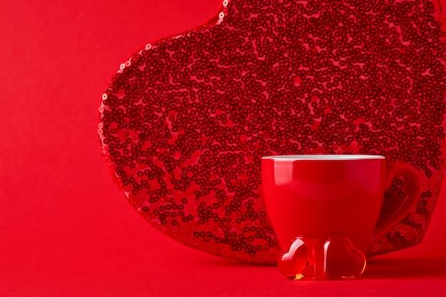 Красная кружка и два сердца и большая коробка позади них на алом или красном фоне. плоская композиция. вид сверху, копия пространства.
