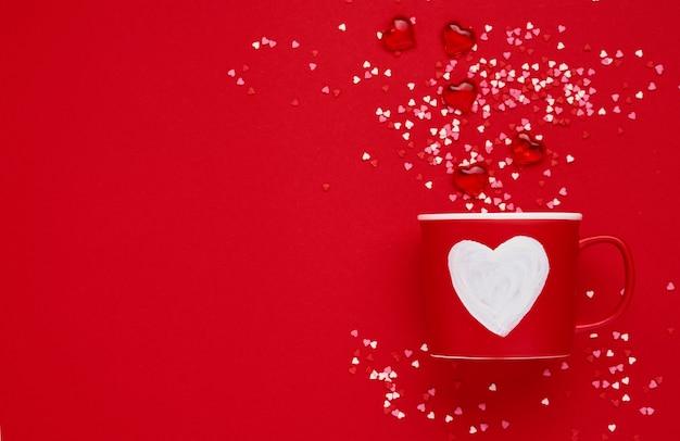 Красная кружка с нарисованным сердцем на красном фоне. плоская композиция. концепция дня святого валентина. вид сверху, копия пространства.