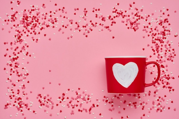 Red cup mug with with painted heart, sugar and chocolate hearts on pink table. flat lay composition. valentines day concept. top view, copy space.