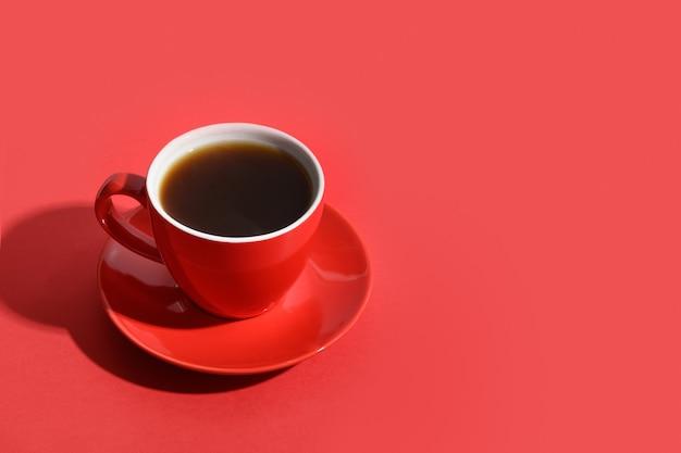 赤い背景の上のコーヒーと豆の赤いカップ