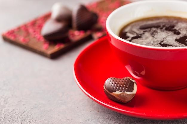 회색 배경 위에 심장 모양에 커피와 초콜릿 사탕의 빨간 컵을 닫습니다. 발렌타인 데이 개념.