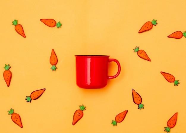 黄色のコーヒーとイースタークッキーのニンジンの赤いカップ