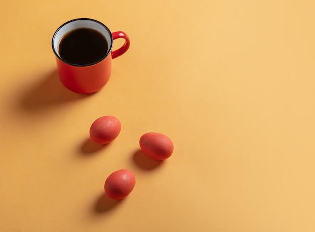 黄色のコーヒーとイースターエッグの赤いカップ