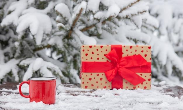Красная чашка кофе и подарочная коробка на деревянном столе в снегу