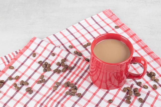 テーブルクロスに豆とコーヒーの赤いカップ