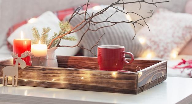 枕と燃えるろうそくのソファとトレイにお茶の赤いカップ。居心地の良い家のコンセプト