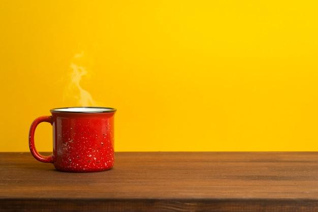 Красная чашка на желтом фоне. винтажная чашка для чая или кофе на деревянном столе. утро, блюда и напитки концепции.