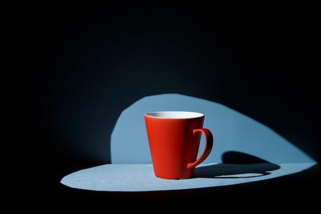 Красная чашка на синей поверхности с прожектором