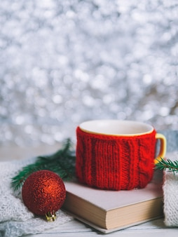 Red cup of tea or coffee with book and christmas tree branches