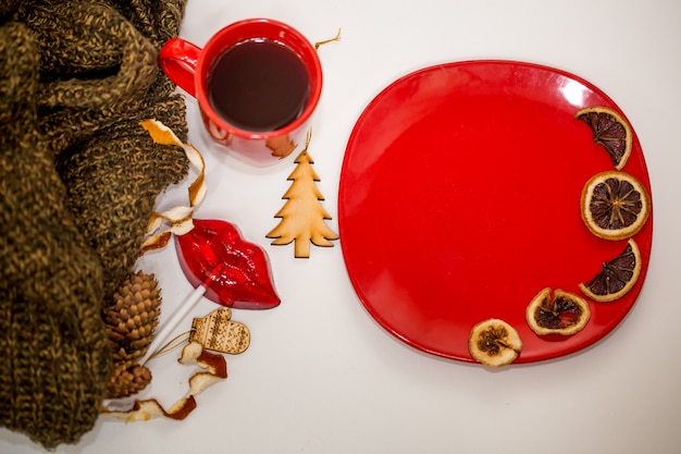 Red cup of tea, plate with dried orange slices and decorative elements