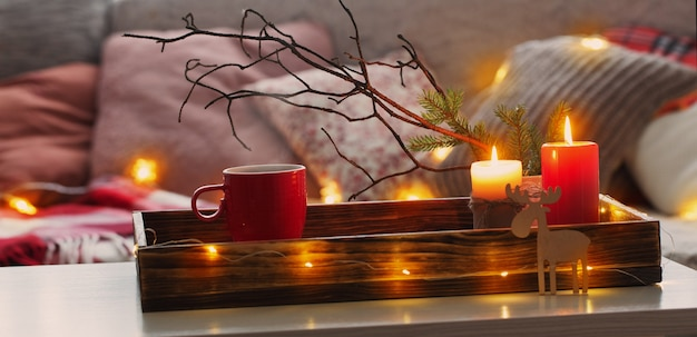 Red cup of tea on tray with burning candles near sofa with pillows