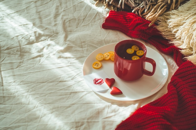 Red cup of tea and two hearts cookies, a note with a kiss on a white bed