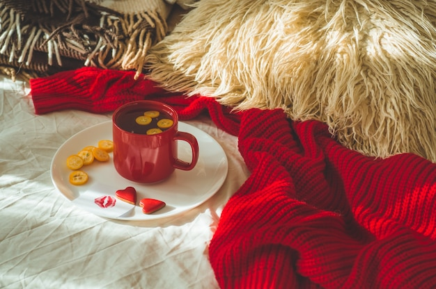 Red cup of tea with kumquat and two hearts cookies on a white bed