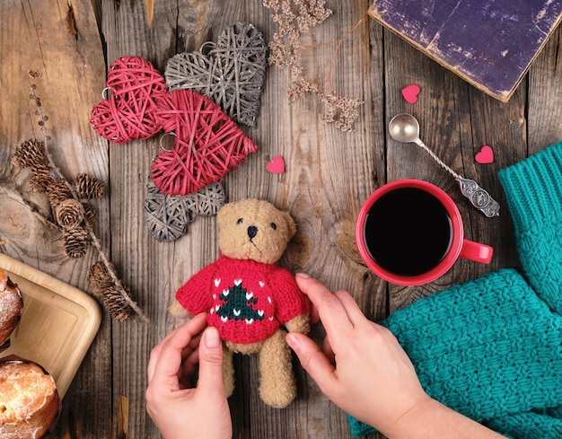 Red cup with black coffee and a little teddy bear in a red sweater