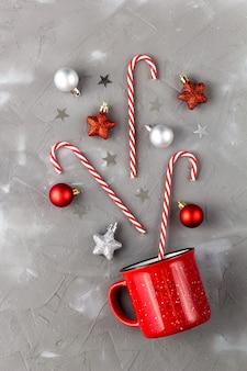 キャンディケイン、ボール、灰色の背景に星と赤いカップ。クリスマスと新年のお祝いのコンセプト。