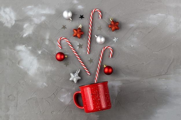 회색 배경에 사탕 지팡이, 공, 별이 있는 빨간 컵. 크리스마스와 새 해 축 하 개념입니다.
