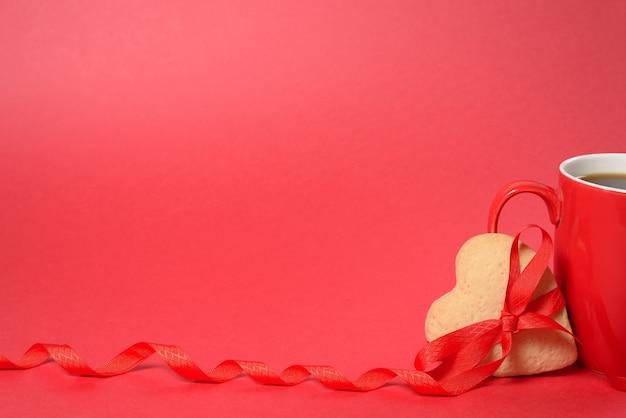 ジンジャーブレッドのハートと赤い背景に赤いリボン、バレンタインデーの休日の赤いカップ。モーションキャプチャコピースペース。
