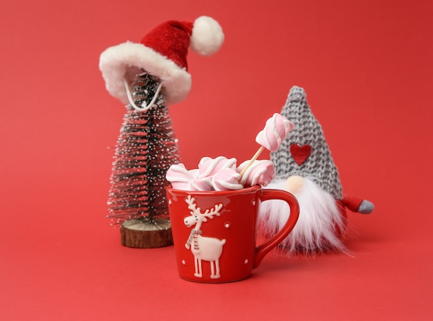 Red cup with hot chocolate and marshmallows and miniature christmas tree in santa claus hat on a red background