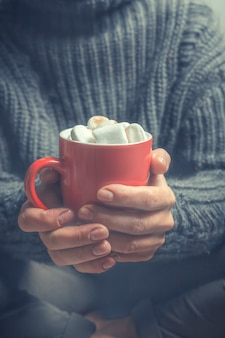 Red cup with hot cocoa and marshmallows in the hands of a woman in a warm cozy jacket close-up