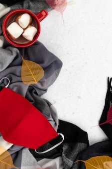 Red cup with hot cocoa, scarf and face mask. flat lay top view new normal autumn winter composition.