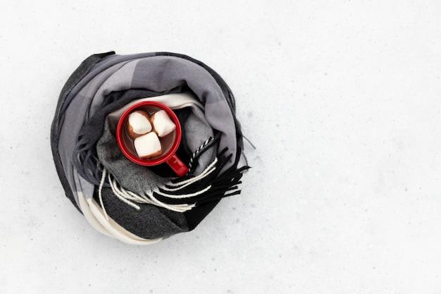 핫 코코아와 빨간 컵 회색 배경에 스카프에 싸여. 평평하다 평면도 가을 겨울 구성.