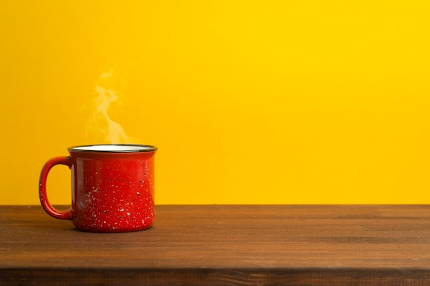 Red cup on a yellow background. vintage cup for tea or coffee on a wooden table. morning, dishes and drinks concept.