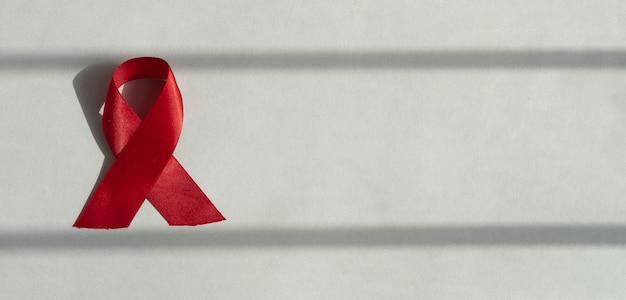 Красная завитая лента как концепция помощи и осведомленности о вич на голубом баннере с копией пространства