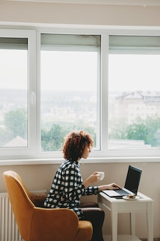 窓の近くのコンピューターでリモートで作業している赤い縮れ毛の白人ビジネスウーマンはお茶を飲み、サンドイッチを食べています