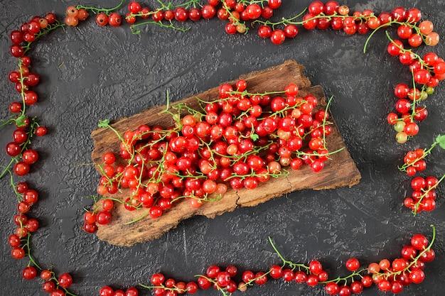 灰色のコンクリート表面に横たわっている赤スグリの果実
