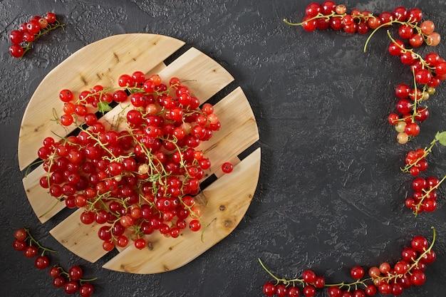 コピースペースとグレーの上に横たわる赤すぐりの果実。