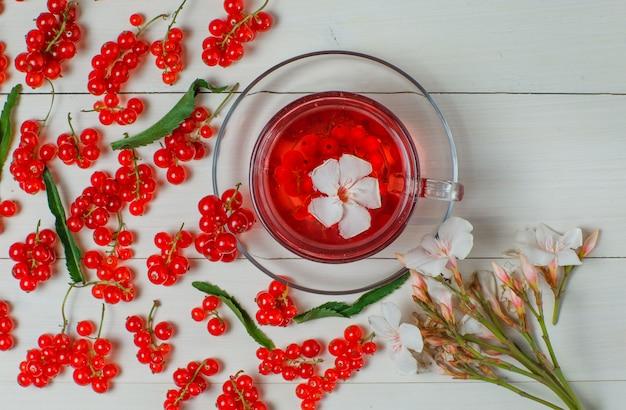 Bacche di ribes rosso con foglie, tè, fiori su legno.