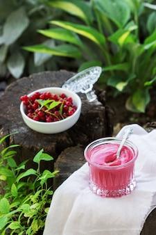 庭の古い切り株に赤スグリのカスタードとスグリの果実。セレクティブフォーカス。