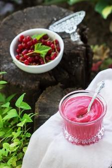 庭の古い切り株に赤スグリのカスタードとスグリの果実。