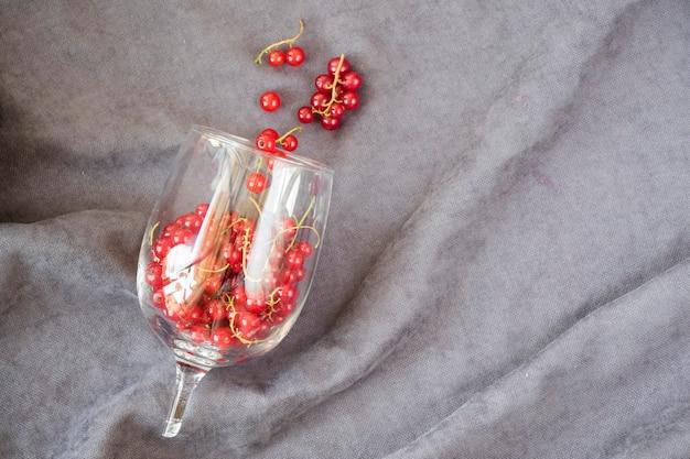Красная смородина в рюмке на фоне серой ткани. большая группа красочных ягод.