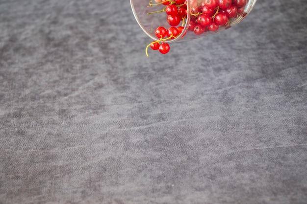 Красная смородина на сером фоне ткани. большая группа красочных ягод.