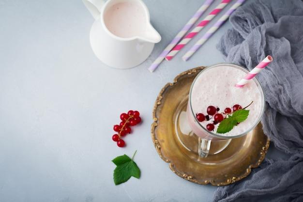 赤スグリのヨーグルトスムージー、灰色のコンクリートの背景にガラスのカップでミルクセーキ。