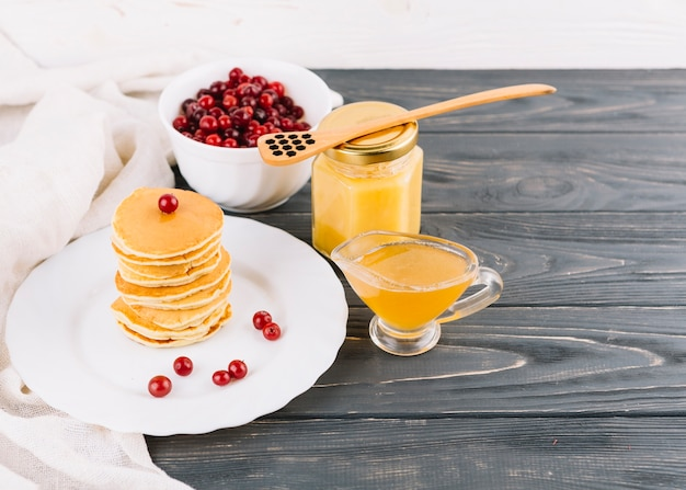 Red currants berries; lemon curd and stacked of pancakes on plate over the wooden table