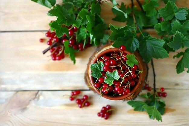 木製のテーブルの上にボウルに赤スグリ。