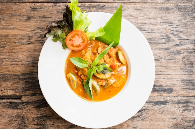Red curry with chicken on wooden background