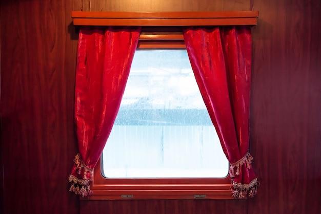 白で隔離の窓の赤いカーテン。古代の列車からのドレープ