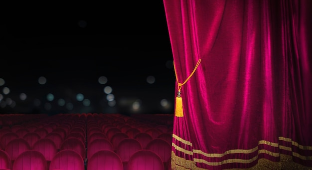 The red curtains of the stage are opening for the theater show