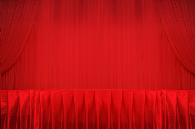 Red curtains and stage and table.