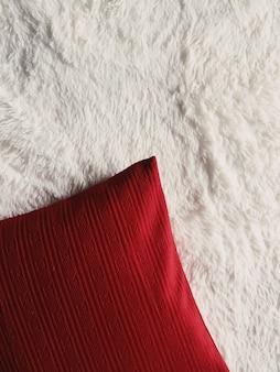 Красная декоративная подушка на белом пушистом клетчатом одеяле плоская планировка