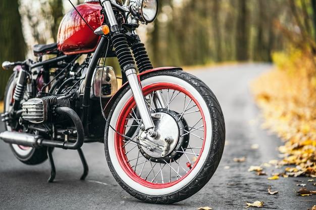 森の中の道路上の赤いカスタム昔ながらのオートバイ
