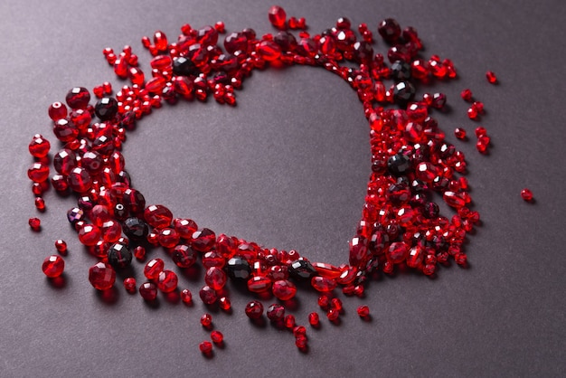 Red cut glass beads on black background, heart shaped