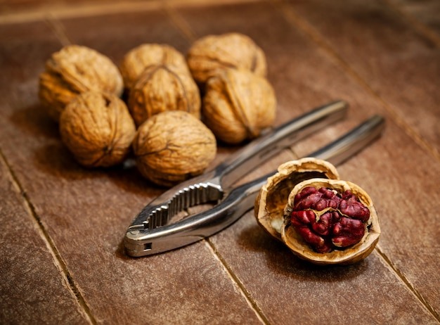 Red danube walnuts with iron nutcracker on wooden surface