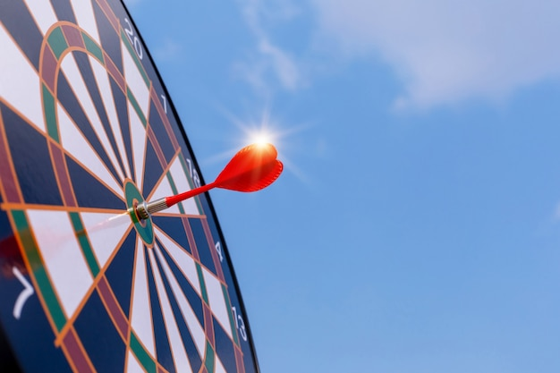 Red dart arrow hit in the target center of dartboard with sky background