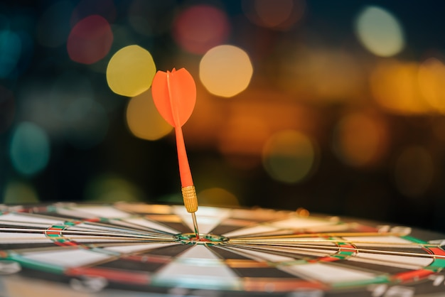 Red dart arrow hitting in the target center of dartboard with city light bokeh background.
